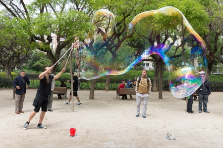 BARCELONA - MAY 16: Unknown street artist makes big soap bubbles in a public park on May 16, 2013 in Barcelona, Spain