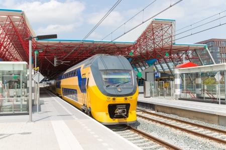 Een trein verlaten van het centraal station van Lelystad, Nederland Stockfoto - 20844727