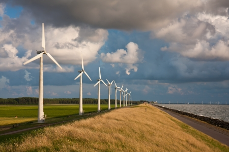 meer: Dutch Windturbines and a cloudscape in the last sunlight of a summer evening Stock Photo