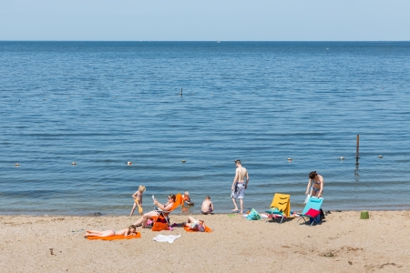 URK- JULY 06: An unknown family is sunbathing and swimming at the first beautiful summer day of the year on July 06, 2013 in Urk, The Netherlands
