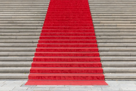 Stone staircase with red carpet photo