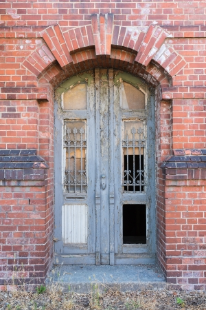 dilapidated: Old dilapidated door in masonry house front