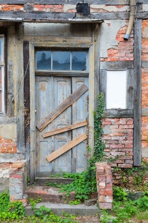 Old dilapidated door in masonry house front