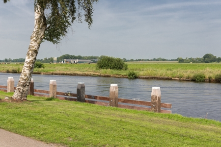 mooring bollards: Canal with wooden bollards in typical Dutch countryside