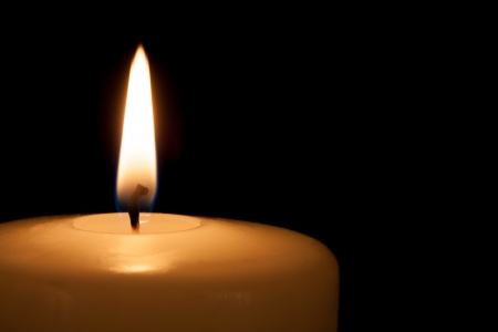 White candle on black background with copy space for text photo