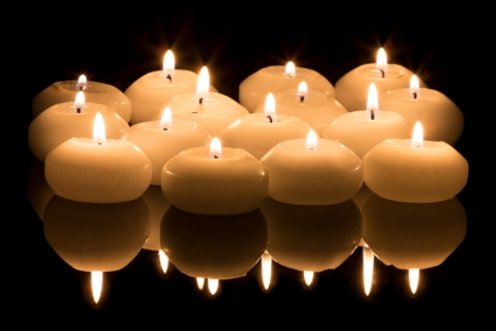 White candles on a black reflecting background photo