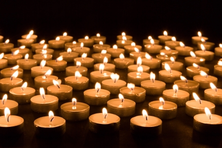 Large group of burning candles at a black background photo