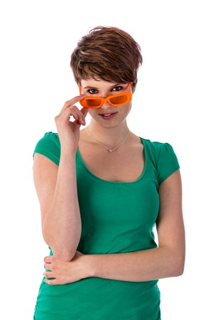 Pretty young woman looking over her orange sunglasses photo