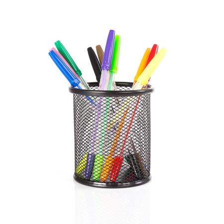 白色の背景上の黒いバスケットでカラフルな鉛筆