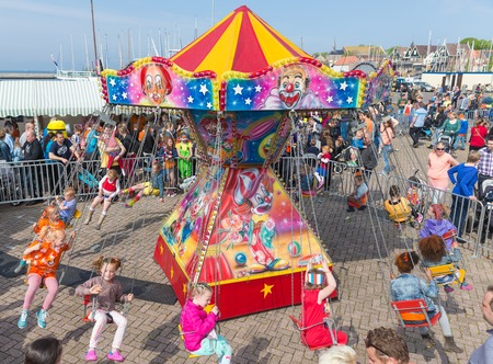 marry go round: URK, THE NETHERLANDS - APR 26  Unknown children have fun in a carousel at a national holiday at the harbor of Urk on April 26, 2014, the Netherlands Editorial