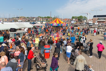 fare: URK, THE NETHERLANDS - APR 26  Unknown people visiting a fare at a national holiday at the harbor of Urk on April 26, 2014, the Netherlands
