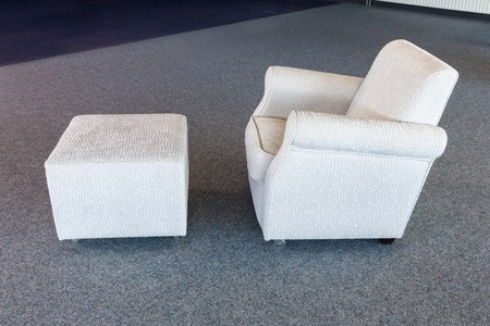 Armchair with white textile upholstery and separate foot-rest photo