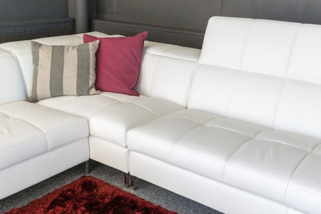 settee: Couch with white upholstery and two pillows