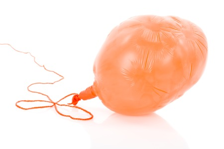 Deflated orange balloon at a rope; isolated over white background
