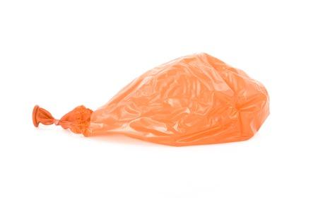 Deflated orange balloon isolated over white background Stock Photo