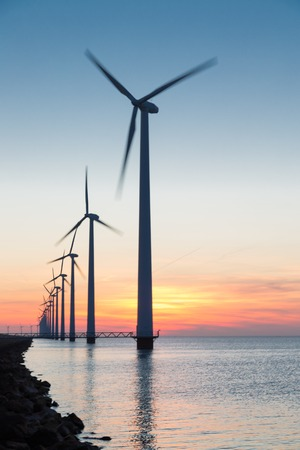 Long row Dutch offshore wind turbines at beautiful sunset photo