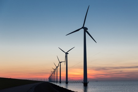 Long row Dutch offshore wind turbines at beautiful sunset