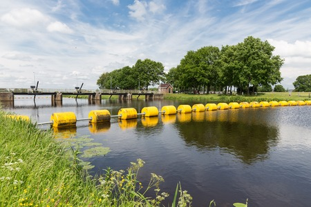 barrage: Barrage in Dutch river Vecht with a floating yellow barricade