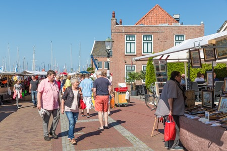fare: URK, THE NETHERLANDS - MAY 31  Tourists visiting a local fare during the fishing days of Urk on May 31, 2014 at the harbor of Urk, the Netherlands