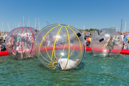 fare: URK, THE NETHERLANDS - MAY 31  Children have fun inside big plastic balloons on the water during a fishing fare on May 31, 2014 at the harbor of Urk, the Netherlands Editorial