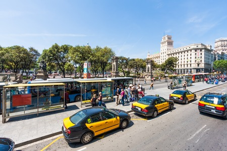BARCELONA, SPAIN - MAY 07: Bus stop with waiting passengers and taxis at Plaza de Catalunya on May 7, 2008 in Barcelona, Spain