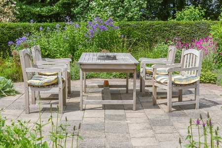 Wooden table and chairs in a beautiful ornamental garden