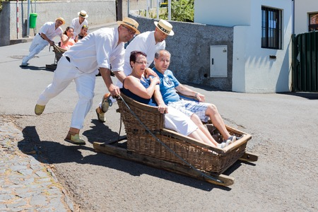 FUNCHAL, MADEIRA - AUG 13: Traditional downhill sledge trip on August 13, 2014 in Madeira, Portugal. Cane sledges were used as traditional local transport. Currently these Toboggan riders are a touristic attraction.