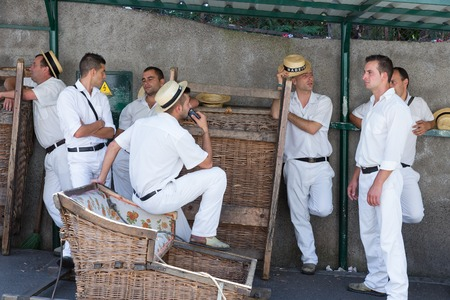 sensation: FUNCHAL, MADEIRA - AUG 13: Toboggan riders waiting for tourists on August 13, 2014 in Madeira, Portugal.  Cane sledges were used as traditional local transport but currently this is a touristic attraction.