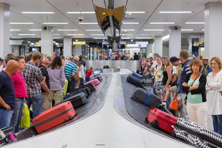 AMSTERDAM, THE NETHERLANDS - AUG 14: Airplane travelers are waiting for their luggage from a conveyor belt at Schiphol airport on August 14, 2014 in Amsterdam, The Netherlands