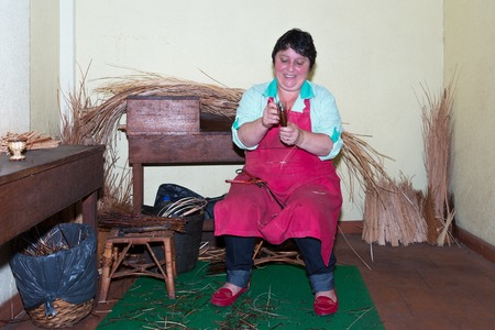 CAMACHA, PORTUGAL - AUG 12: A woman is making reed furniture in a braiding factory on Augustus 12, 2014 at Madeira, Portugal. This is a touristic attraction with demonstrations of this traditional craftsmanship.