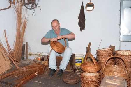 CAMACHA, PORTUGAL - AUG 12: A man is making reed baskets in a braiding factory on Augustus 12, 2014 at Madeira, Portugal. This is a touristic attraction with demonstrations of this traditional craftmanship.