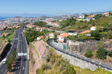Aerial view of Funchal and highway, build against the mountains of Madeira Island, Portugal photo
