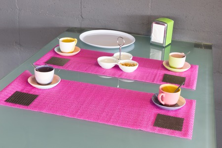 Table in furniture showroom decorated with coffee cups and plates photo