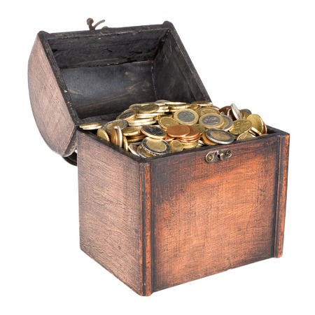 Wooden money chest filled with coins isolated at a white background photo