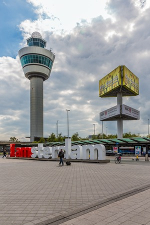 control tower: AMSTERDAM, THE NETHERLANDS - SEP 11: Airport square with control tower, advertising pillar and passing travellers on September 11, 2014 at the airport Schiphol of Amsterdam, the Netherlands
