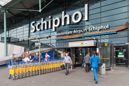 AMSTERDAM, THE NETHERLANDS - SEP 11: Airport entrance with passing travellers and a stewardess on September 11, 2014 at the airport Schiphol of Amsterdam, the Netherlands