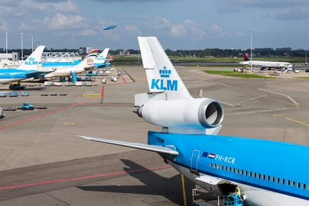 departing: AMSTERDAM, THE NETHERLANDS - SEP 11: Schiphol airport with workers and departing and arriving airplanes on September 11, 2014 at Amsterdam, the Netherlands Editorial