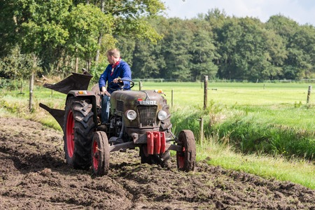 NIEUWEHORNE, THE NETHERLANDS - SEP 27: Farmer riding with an old tractor during the agricultural festival Flaeijel on September 27, 2014, the Netherlands Redactioneel