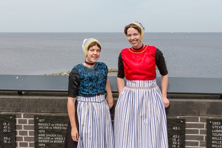 drown: URK, THE NETHERLANDS - JUN 07: Two traditional dressed women from Urk visiting the monument of drown fishermen on June 07, 2014 at the coast of Urk, the Netherlands
