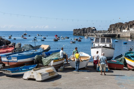 CAMARA DE LOBOS, PORTUGAL - AUG 04: Harbor with fishermen and fishing ships at the bay of Camara de Lobos on August 04, 2014 at Funchal, Portugal