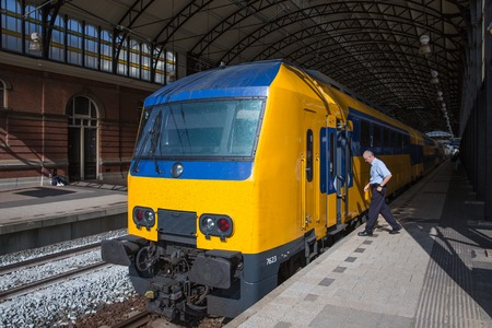 spoor: THE HAGUE, THE NETHERLANDS - SEP 18:  Conductor getting in a train ready to start at the train station of Holland Spoor on September 18, 2014 in The Hague, the Netherlands