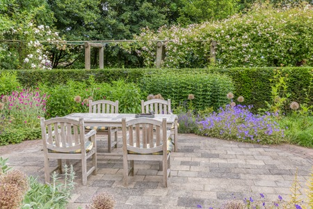 garden furniture: Wooden table and chairs in a beautiful ornamental garden