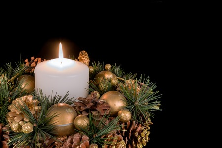 Christmas decoration with a white candle and pine apples on a black background photo