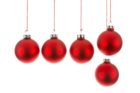 Red Christmas balls hanging at a rope over white photo