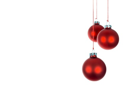 Three hanging Christmas balls over a white background photo