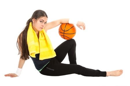 Pretty woman in sports wear sitting on floor with basketball, isolated on white background photo