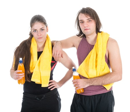 sports wear: Man and woman in sports wear relaxing with orange juice, isolated at white background