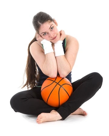 sports wear: Pretty young woman in sports wear sitting on floor with a basketball, isolated over white Stock Photo