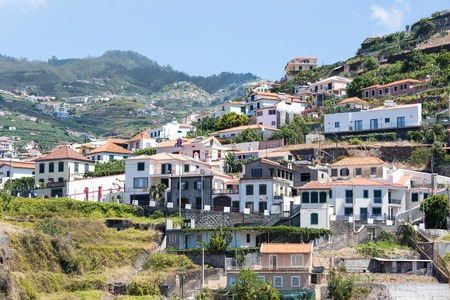 Little village build against a mountain slope at Madeira Island, Portugal photo
