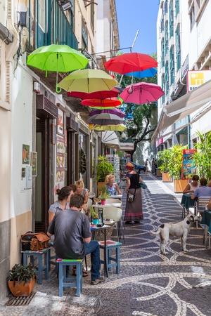 FUNCHAL, PORTUGAL - 6 augustus: Toeristen zitten op het terras van een klein restaurant in Funchal op 6 augustus 2014 in Funchal, de hoofdstad van Madeira, Portugal Stockfoto - 36841131